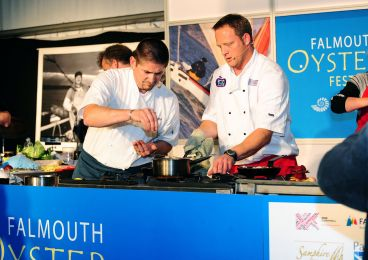 Two chefs give a cooking demonstration at the Falmouth Oyster Festival.