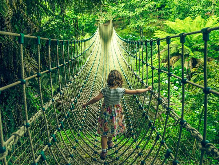 A girl crosses the rope bridge at The Lost Gardens of Heligan.