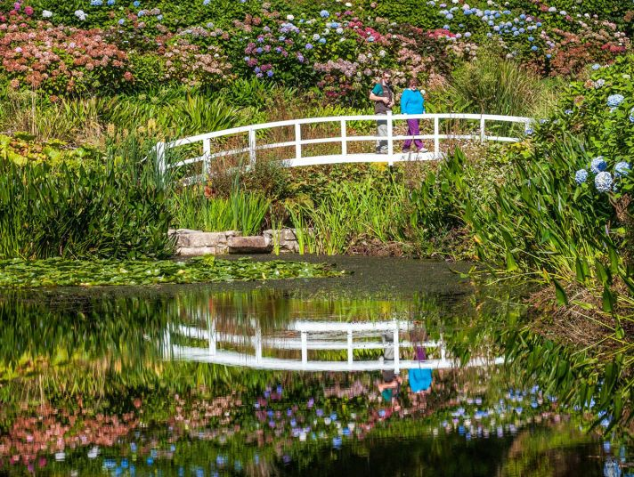 Holidaymakers cross a bridge over the Trebah garden pond.