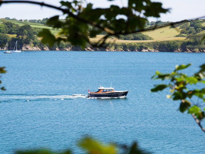 A boat on the River Fal seen through branches.