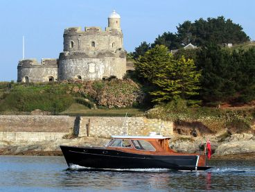 The Nare's motor launch, Alice Rose, passing the medieval St Mawes castle.