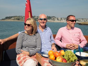 Friends enjoy sun and fruit while sailing the River Fal.