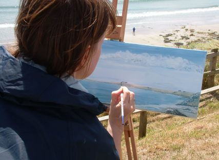 A woman paints the Cornish coast during an art holiday.