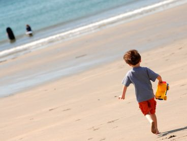 A little boy runs along Carne Beach towards the sea.