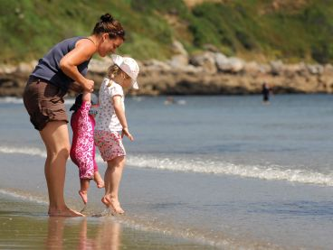 A mother and her two children play on Carne Beach on the south coast of Cornwall.