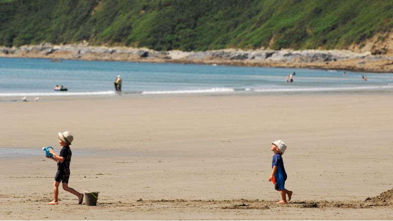 Two children play on the sand of Carne Beach, a secret beach near Truro in Cornwall.