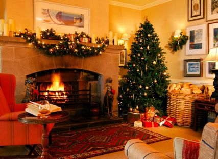 The Nare hotel, decorated for Christmas with a tree, festive adornments and an open fire.