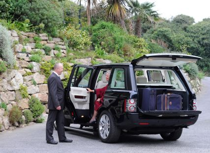 The Nare hotel's chauffeur helps a guest out of the hotel's private Range Rover.