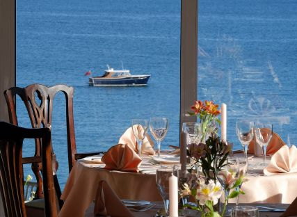 The Nare hotel dining room, with tables set and panoramic sea views.