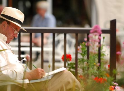 A man jots in a notebook as he sits in The Nare hotel gardens.