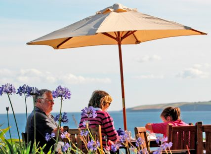 A family sits beneath a parasol at The Nare hotel.
