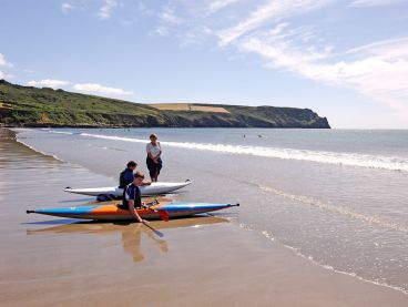 Two holidaymakers sit in kayaks on Carne Beach.