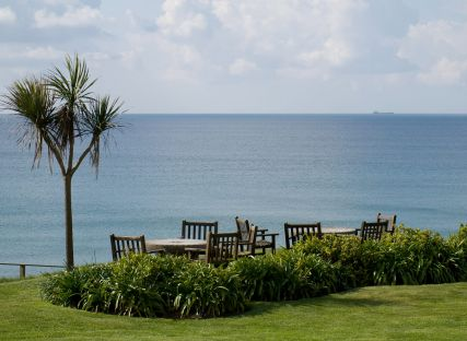 Garden furniture in The Nare hotel gardens and the sea beyond.