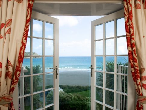 French doors leading to a sea view balcony, at The Nare hotel.