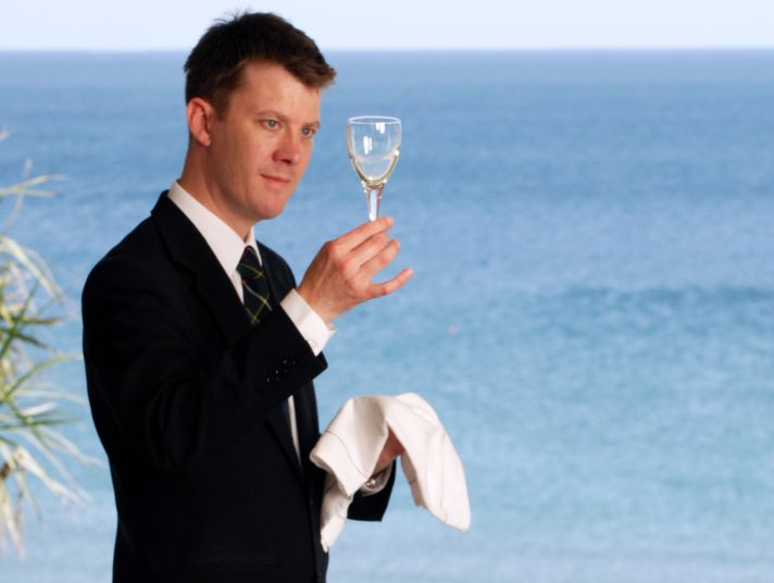 The Nare hotel's Restaurant manager inspects a wine glass.