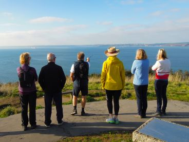 A group of guests taking in the view from St Anthony Head