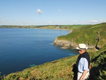 A man looks back at the hotel from the coast path